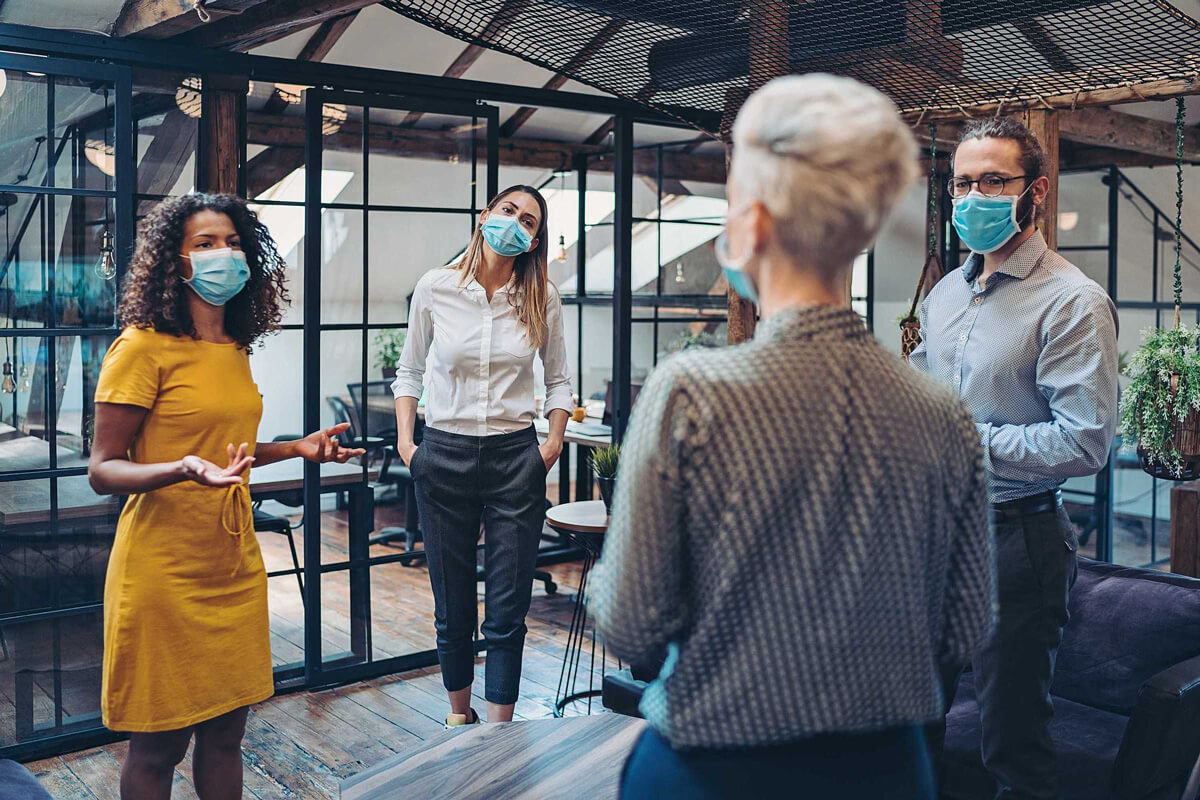 client journey - four people standing in a circle in an office talking with face masks on