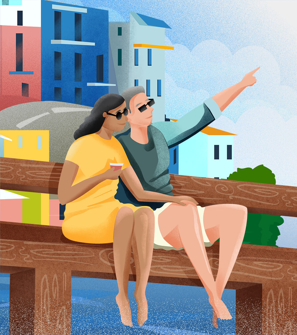 savor - a couple sitting on a pier enjoying the ocean view