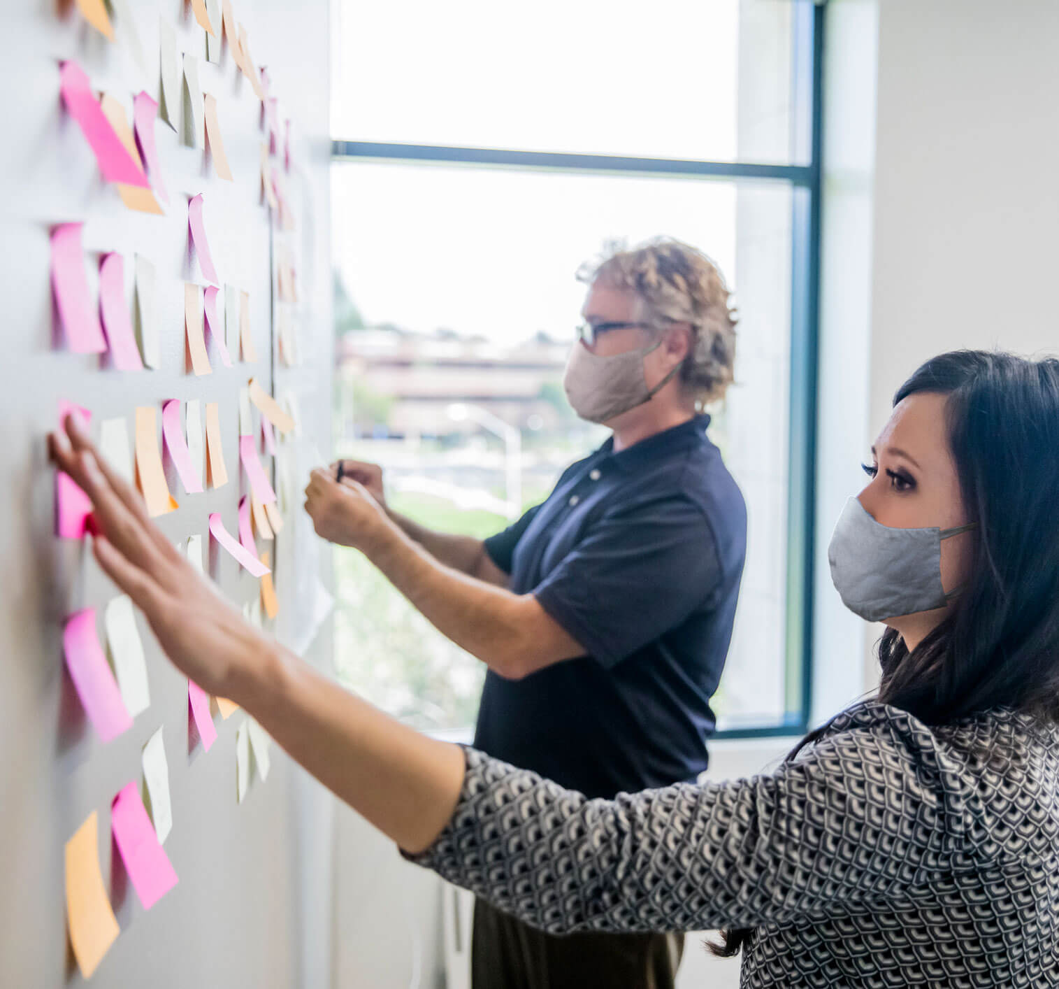 strategic growth - a young woman and man looking at a planning board covered in post its