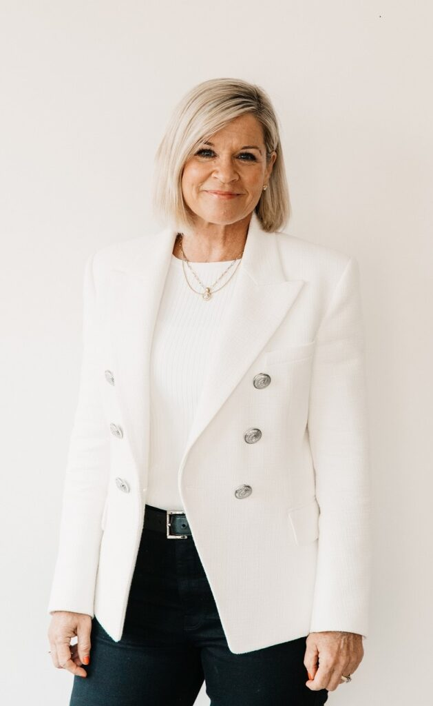 team - Pamela Lauper standing against a white wall smiling at the camera