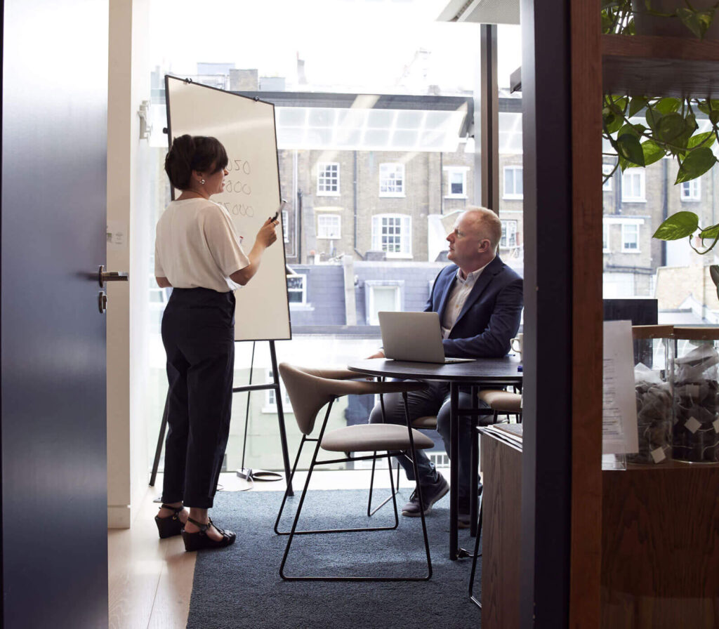 strategic sale - a woman standing at a whiteboard in an office talking to a man who is sitting in front of her