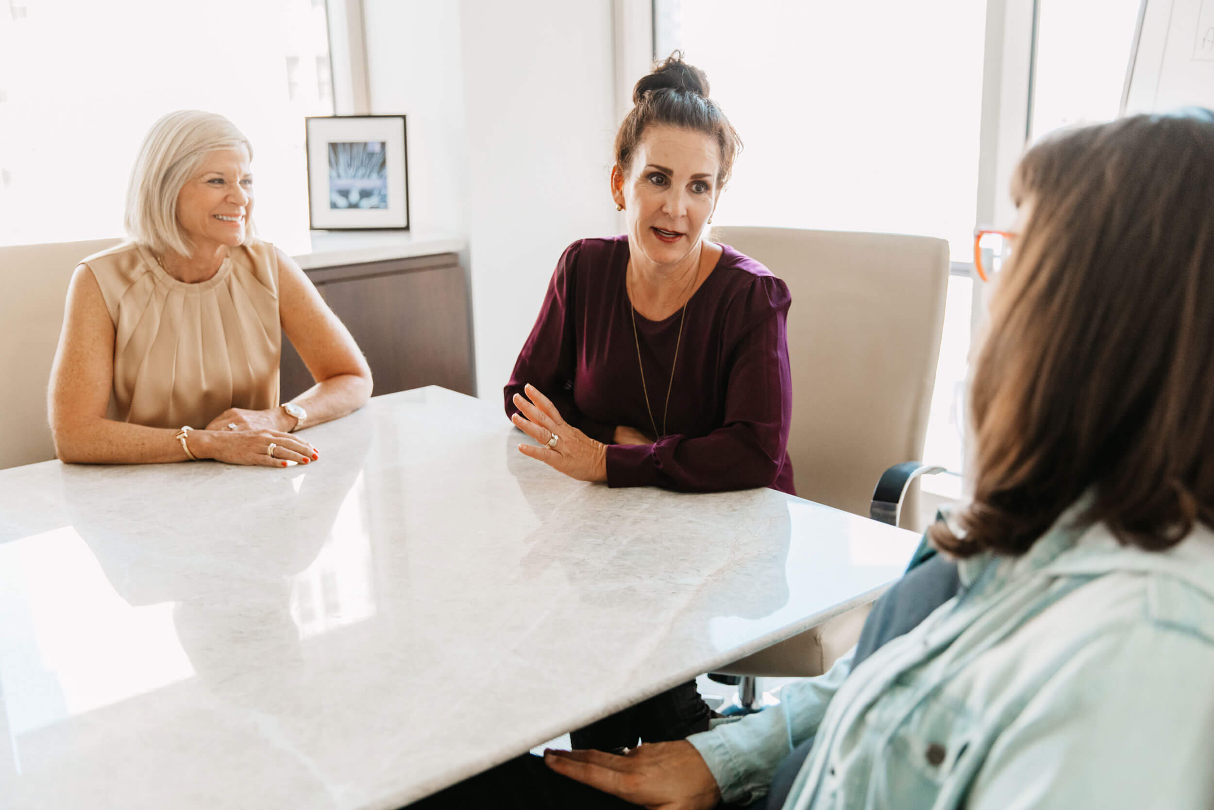 we guide - three women sitting at a conference table talking